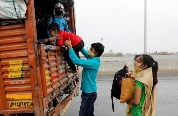 Sushil Kumar, a migrant worker, helps his son get inside a truck as he returns to his village wit his family, during a 21-day nationwide lockdown to limit the spreading of coronavirus disease (COVID-19), in Ghaziabad, on the outskirts of New Delhi, 27 March, 2020 (Photo: Reuters/Adnan Abidi).