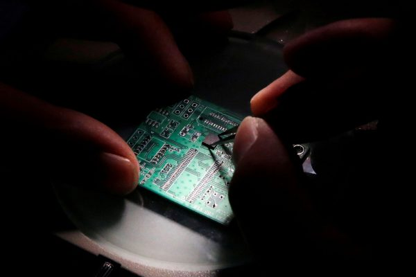 A researcher plants a semiconductor on aninterfaceboard, Beijing, China, 29 February 2016 (Photo: Reuters/Kim Kyung-Hoon).