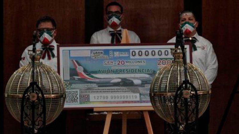 Trabajadores de la lotería junto a una replica gigante del boleto para la rifa del avión presidencial (Foto: Cuartoscuro)