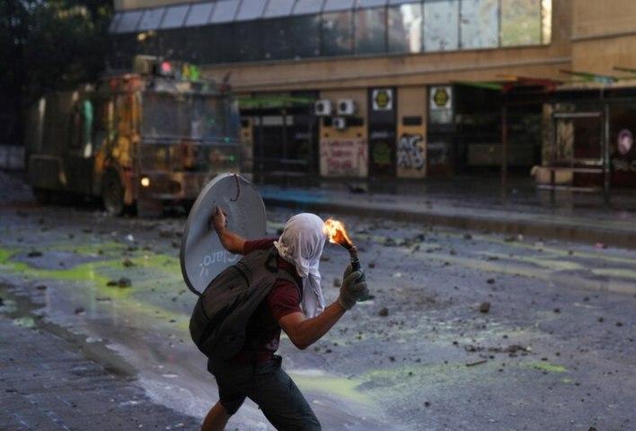 Un manifestante lanza un cóctel molotov contra un vehículo de la policía antidisturbios (REUTERS/Pablo Sanhueza)