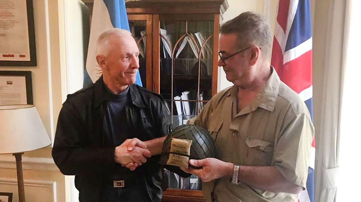 John Curd y Jorge Melinchuk en la embajada argentina en Londres. El veterano inglés le devolvió el casco que se había llevado de las islas como recuerdo de guerra