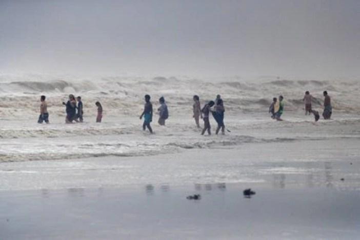 Los visitantes de la playa en Galveston, Texas, juegan con las olas del huracán Hanna el 25 de julio de 2020. REUTERS/Adrees Latif