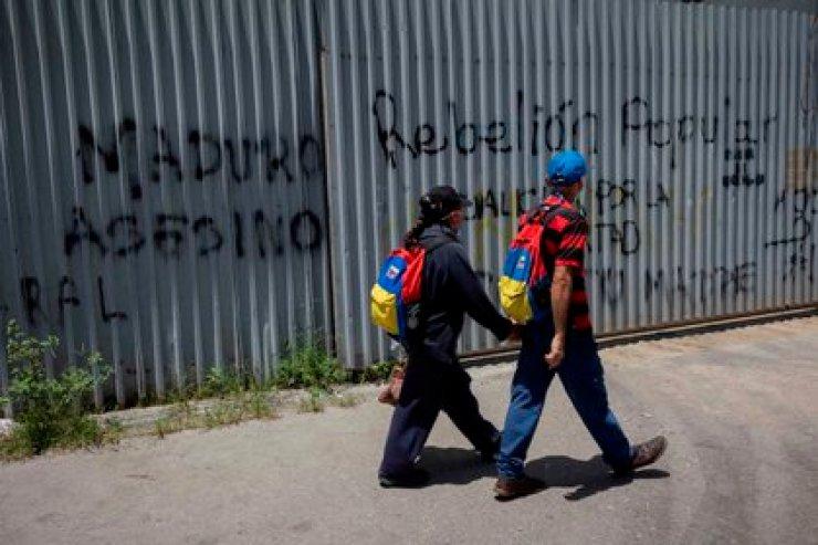 Dos personas caminan ante varios grafitis con mensajes de rechazo al presidente de Venezuela, Nicolás Maduro, en Caracas (Venezuela).EFE/ Rayner Peña