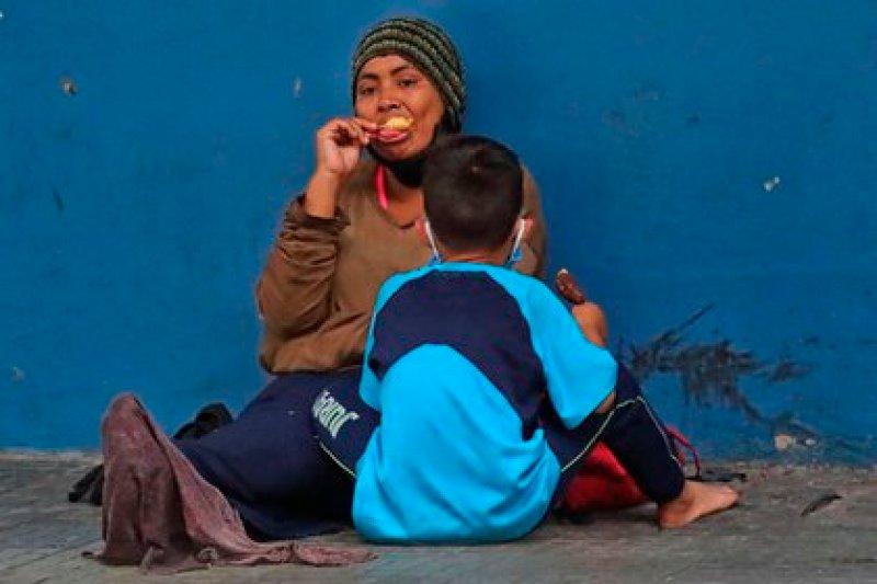 Una mujer y un niño permanecen sentados en una calle en la que piden diner este miércoles en Tegucigalpa (EFE/ Gustavo Amador)