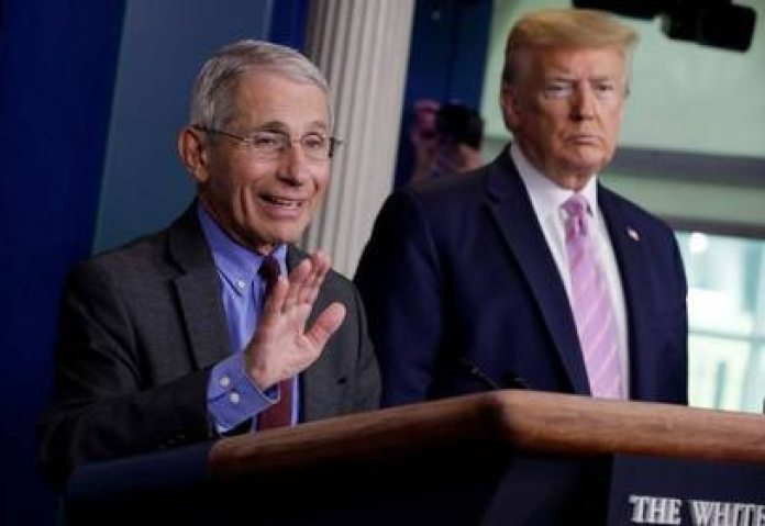 Fauci at press conference, observed by Donald Trump (Reuters)