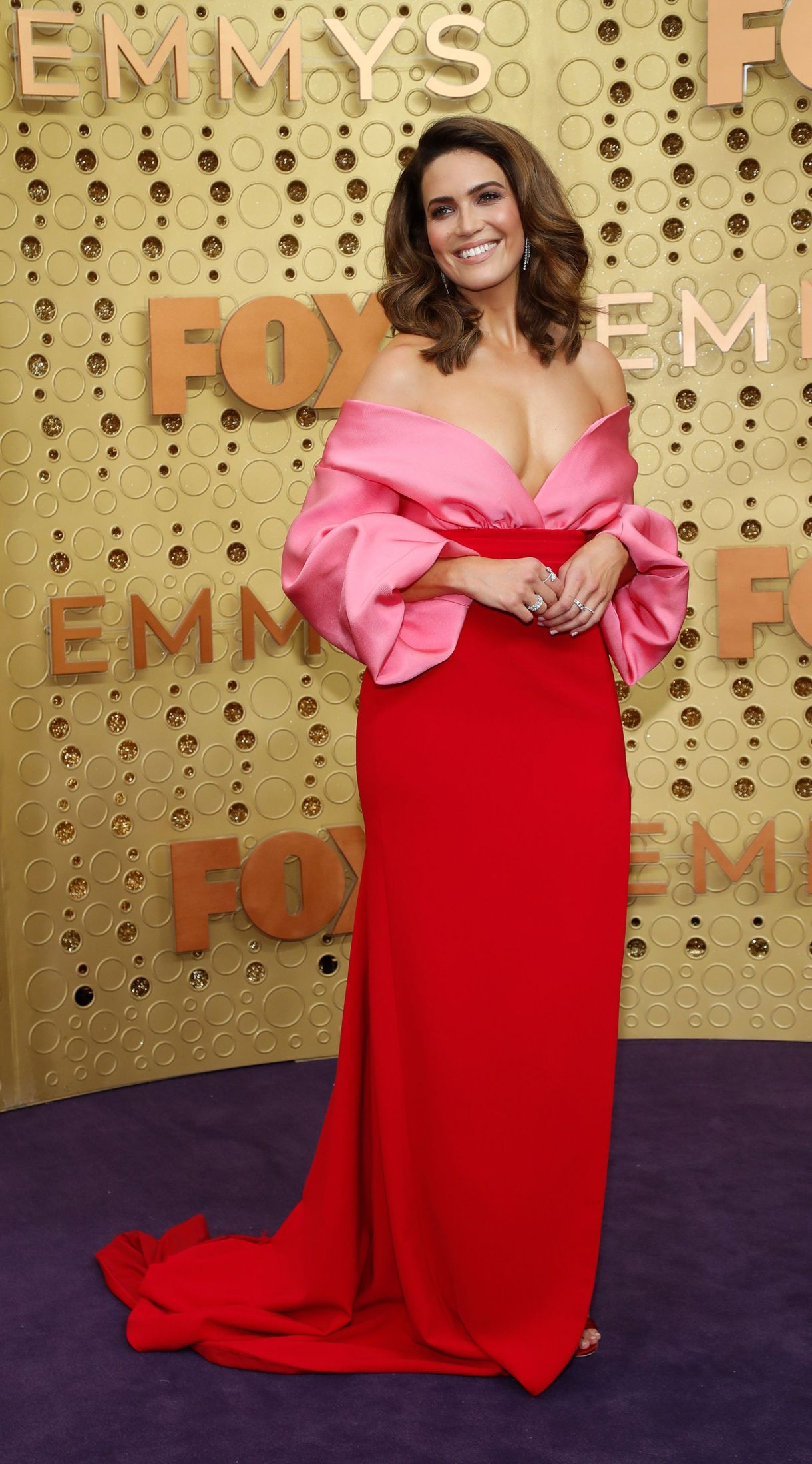 Mandy Mooredeslumbró en la alfombra violeta con un vestido bicolor de Brandon Maxwell en rosa y rojo de hombros caídos y gran escote y cola. Completó su look con sandalias rojas, anillos y aros de brillantes