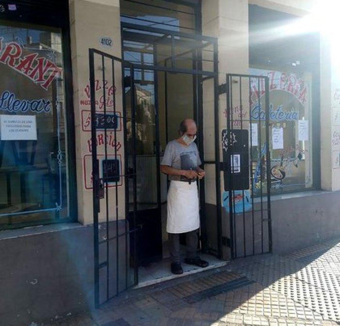 Juan en la puerta de su pizzería, esperando que llegue algún pedido a su celular