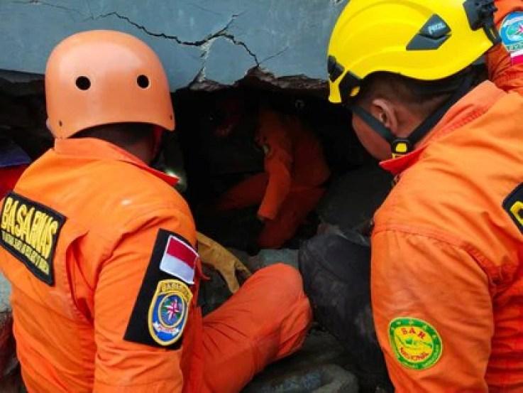 Miembros del equipo de rescate buscan sobrevivientes entre los escombros luego del terremoto de Indonesia