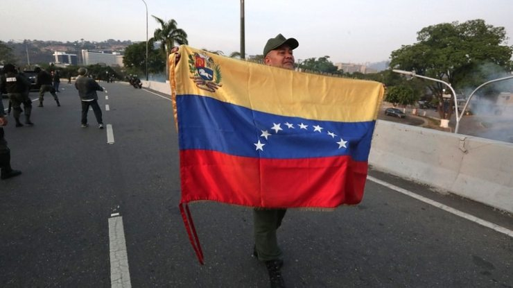 Un militar despliega una bandera en la base de La Carlota, al este de Caracas, donde ha sido conducido el opositor Leopoldo López, tras ser liberado este martes y donde se ha reunido con el presidente Juan Guaidó, que ha anunciado que los militares han dado el paso para unirse a él. EFE/Rayner Peña