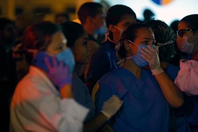 Una mujer llora mientras otra habla por teléfono (MAURO PIMENTEL / AFP)