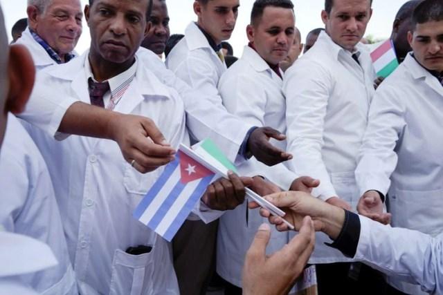 Médicos cubanos reciben banderas cubanas e italianas durante una ceremonia de despedida antes de partir a Italia para ayudar con la propagación del brote de la enfermedad por coronavirus