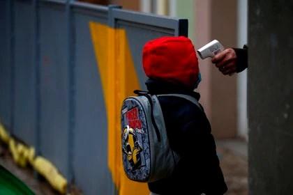 Una profesora toma la temperatura a un alumno de la Escuela Rubén Dario de Barcelona antes de entrar a clase. EFE/Quique Garcia/Archivo