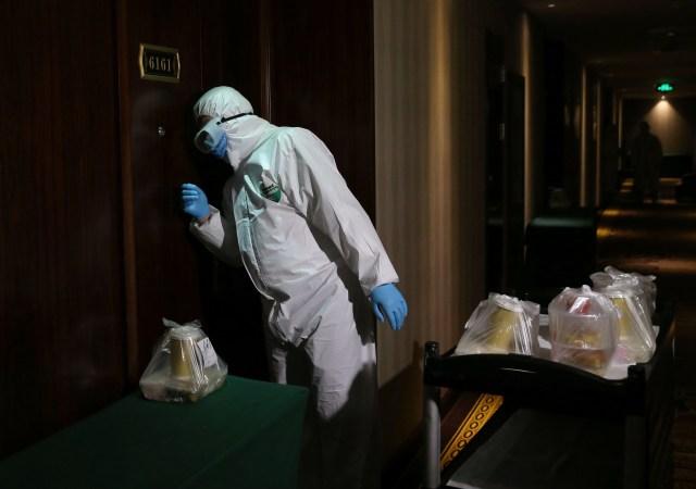 Un trabajador golpea la puerta de una habitación de hotel para entregar alimentos a personas que se encuentran aislados en cuarentena