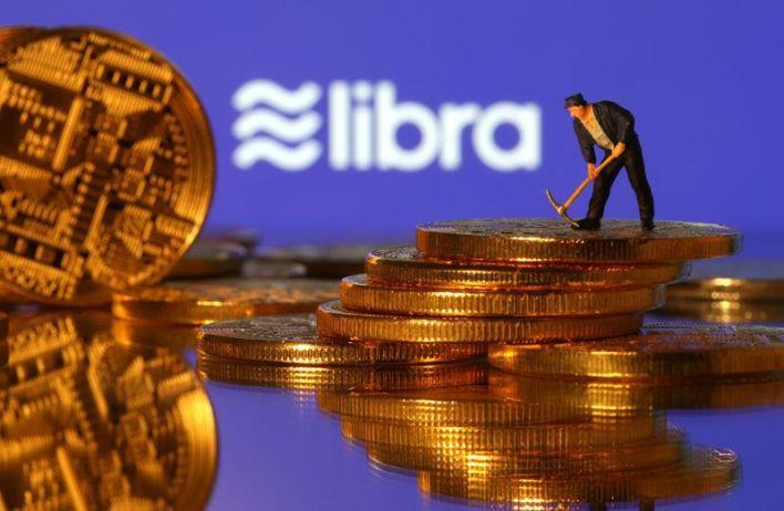 Una pequeña figura de juguete se para sobre las representaciones de la moneda virtual frente al logotipo de Libra en esta ilustración, el 21 de junio de 2019. REUTERS/Dado Ruvic/Illustración