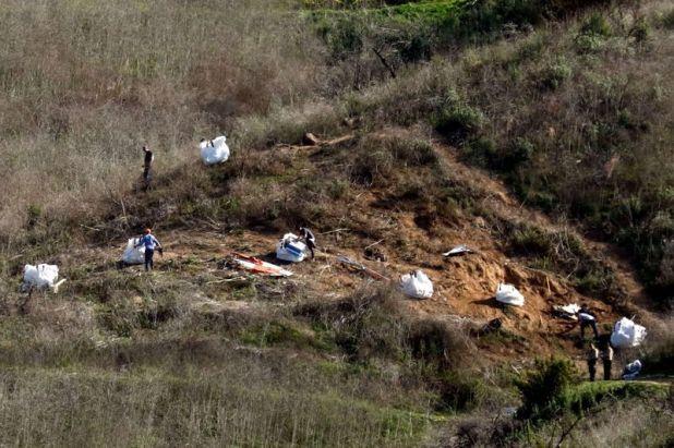Personal recoge escombros mientras trabaja con investigadores en el lugar del accidente de helicóptero de la estrella de la NBA Kobe Bryant en Calabasas, EEUU, 28 enero 2020 (Reuters)