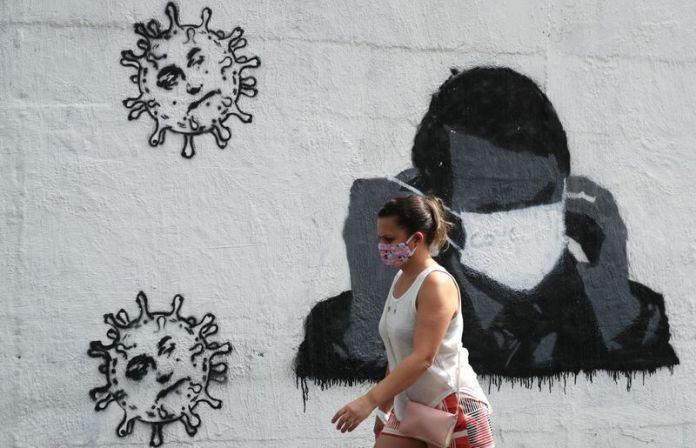 Una mujer pasa por delante de un grafiti que muestra al presidente de Brasil, Jair Bolsonaro, ajustando su máscara protectora, en medio del brote de coronavirus en Río de Janeiro el 2 de julio de 2020. REUTERS/Sergio Moraes