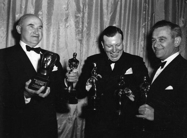 1946: Samuel Goldwyn con el Oscar a mejor película y el premio Irving G. Thalberg Memorial; en el medio, Harold Russell con el de actor secundario y a la derecha, con el de mejor director, William Wyler