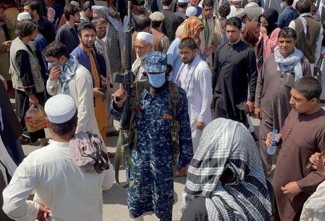 FOTO DE ARCHIVO: Un miembro de las fuerzas de seguridad talibán monta guardia entre la multitud que pasa por una calle de Kabul, Afganistán,  REUTERS/Stringer