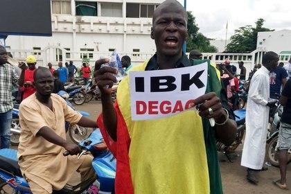 """un simpatizante de la oposición al gobierno de Mali en los festejos ante la noticia de un supuesto golpe de Estado contra el presidente. En su cartel, se lee: """"Fuera IBK (Ibrahim Boubacar Keita)"""". REUTERS/Rey Byhre"""