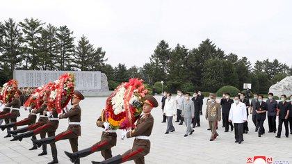 Oficiales norcoreanos caminan frente a las estatuas de Kim Il Sung y Kim Jong Il. KCNA via REUTERS