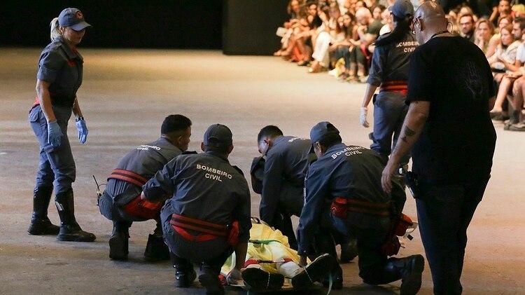 Tales Cotta es atendido por los paramédicos tras desplomarse en la pasarela (AP)