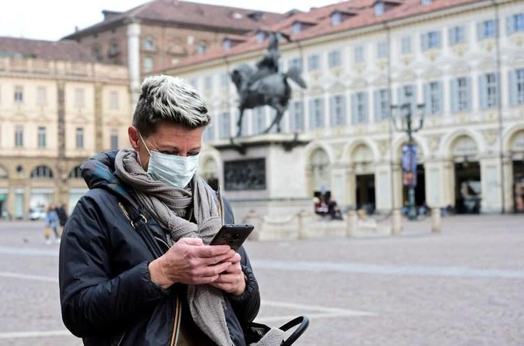Una mujer con una mascarilla usa su teléfono móvil, en Turín (REUTERS/Massimo Pinca)