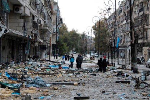 Varios habitantes mientras inspeccionan una calle cubierta de escombros en un barrio del este de Alepo (Siria). EFE/STR