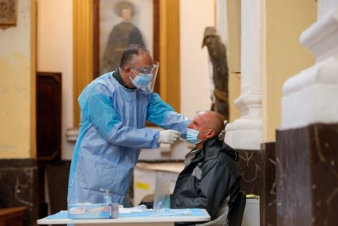 A member of medical staff wearing protective clothing takes a sample from a man at the coronavirus disease (COVID-19) testing center at the San Severo fuori le mura church in Naples, Italy, on November 18, 2020. REUTERS / Ciro De Luca