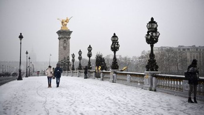 Parisinos caminan por el puente Alexandre III el 16 de enero de 2021 durante la nevada en París (Foto de MARTIN BUREAU / AFP)