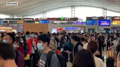 Personas en una estación de trenes en Wuhan