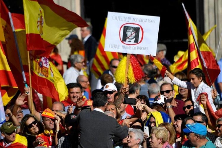 Xavier García Albiol, líder del Partido Popular en Cataluña, saluda a la multitud frente a un cartel opositor a Carles Puigdemont (AFP)