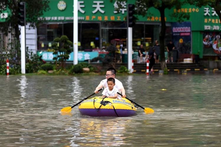 Una hombre con un niño sobre un bote inflable. (REUTERS)