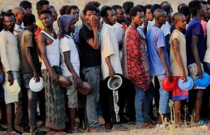 Etíopes que huyeron de la guerra en la región de Tigray, hacen cola para recibir raciones de alimentos en el campamento de Um-Rakoba, en la frontera entre el Sudán y Etiopía, en el estado de Al-Qadarif, Sudán, el 19 de noviembre de 2020. (REUTERS/Mohamed Nureldin Abdallah)