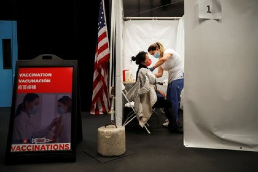 A healthcare worker administers an injection of the Moderna COVID-19 vaccine to a woman at an pop-up vaccination center operated by SOMOS Community Care during the coronavirus disease (COVID-19) pandemic in Manhattan in New York City,