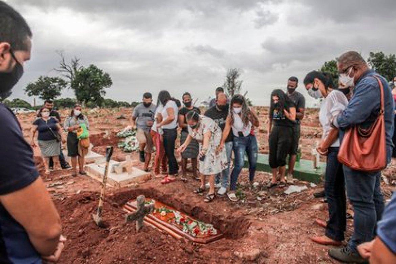 Familiares lloran la muerte por covid-19 de un ser querido, durante su entierro hoy, en un cementerio del norte de Río de Janeiro (Brasil). EFE/ André Coelho