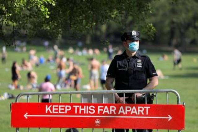 Un oficial del Departamento de Policía de la Ciudad de Nueva York (NYPD) con una mascarilla se encuentra en la entrada del Sheep Meadow en Central Park durante el brote de coronavirus (COVID-19), en Manhattan, Nueva York, EEUU. 15 de mayo de 2020. REUTERS/Andrew Kelly/File Photo
