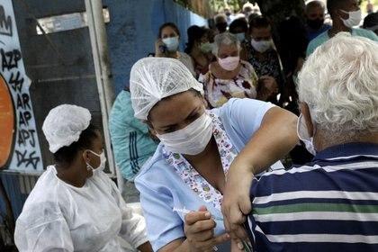 FOTO DE ARCHIVO. Una trabajadora de salud vacuna a un adulto mayor contra la enfermedad del COVID-19 en la ciudad de Sao Goncalo, cerca de Río de Janeiro, Brasil. Febrero 18, 2021. REUTERS/Ricardo Moraes