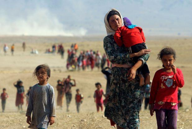 Personas desplazadas de la minoría Yazidi huyen de la violencia de las fuerzas leales al Estado islámico en la ciudad de Sinjar, y caminan hacia la frontera siria en la gobernación de Al-Hasakah, Irak, el 11 de agosto de 2014 (REUTERS/Rodi Said)