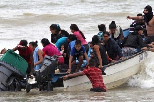Migrantes venezolanos, que fueron deportados recientemente, llegan a la costa en la playa Los Iros después de su regreso a la isla, en Erin, Trinidad y Tobago, el 24 de noviembre de 2020 (Lincoln Holder / Cortesía del Newsday / Folleto vía REUTERS)