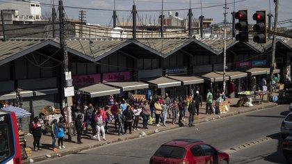 Filas de gente esperando colectivos, en cercanías de la misma estación de Laferrere. Un sábado casi normal