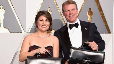 Brian Cullinan y Martha Ruiz, los dos representantes de PricewaterhouseCoopers con custodiando las valijas en las que están los premios.