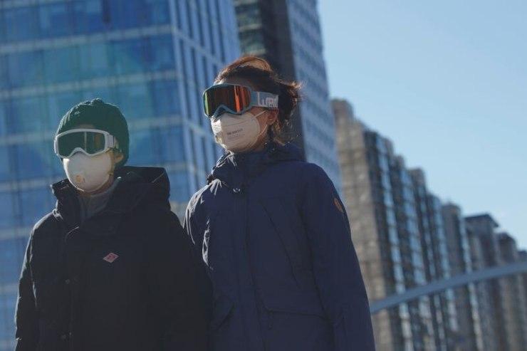 Personas con gafas de nieve y máscaras faciales en una calle, mientras el país es golpeado por el brote del novedoso coronavirus, en el distrito central de negocios de Beijing, China, el 16 de febrero de 2020 (Reuters)