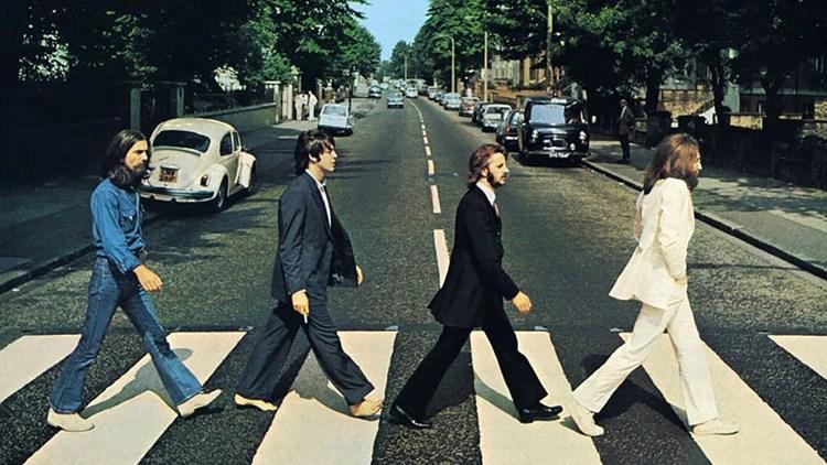 Los cuatro Beatles y Cole observando al fondo de la imagen en la tapa del disco