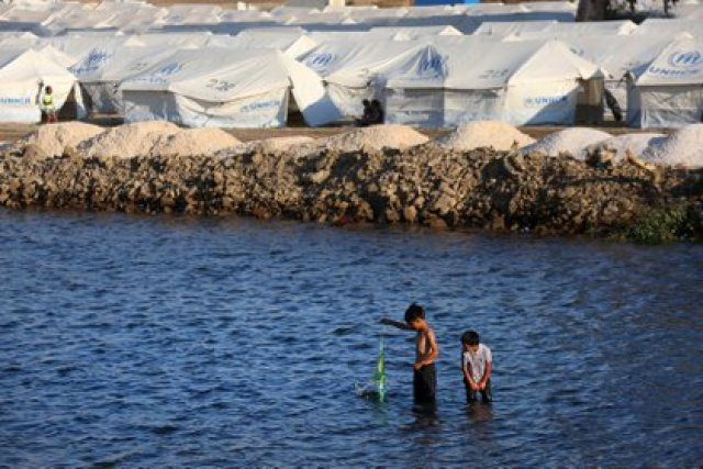 Moria (Greece), 13/09/2020.- Two boys play in the sea in the new refugee camp at Kara Tepe on Lesbos island, Greece, 13 September 2020. Some two hundred refugees and migrants, mostly families, have already entered the camp after they were examined for Covid-19, while 12 were found positive to the virus. (Grecia) EFE/EPA/ORESTIS PANAGIOTOU