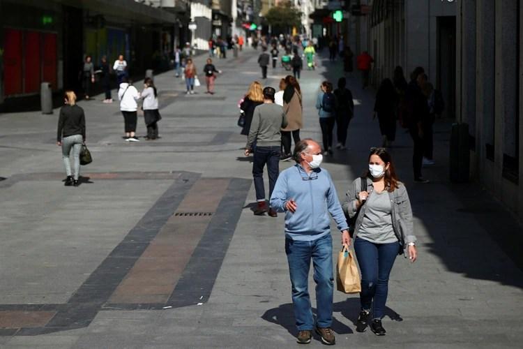 Dos peatones con mascarillas en la calle de Preciados, en el centro de Madrid (Reuters)