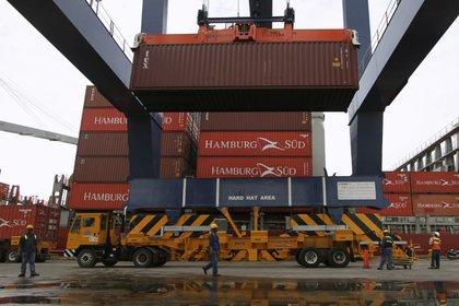 Foto de archivo. Una grúa carga un camión con un contenedor mientras los trabajadores supervisan la operación en el Puerto de Cartagena, Colombia, 14 de mayo, 2012. REUTERS/Joaquín Sarmiento