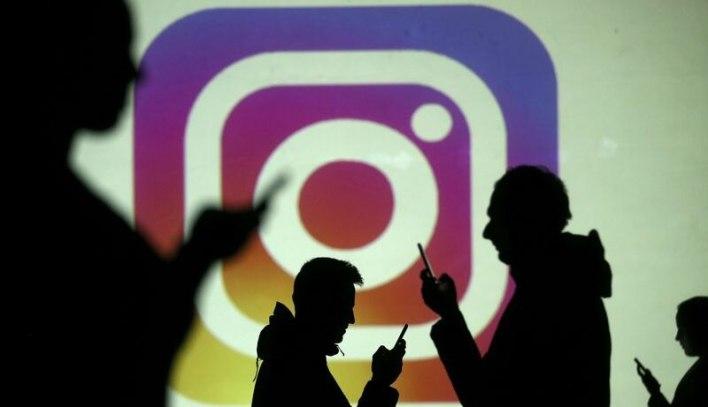 Imagen de archivo de siluetas de usarios de teléfonos móviles frente a una pantalla con el logo de Instagram. 28 de marzo, 2018.  REUTERS/Dado Ruvic/Illustration