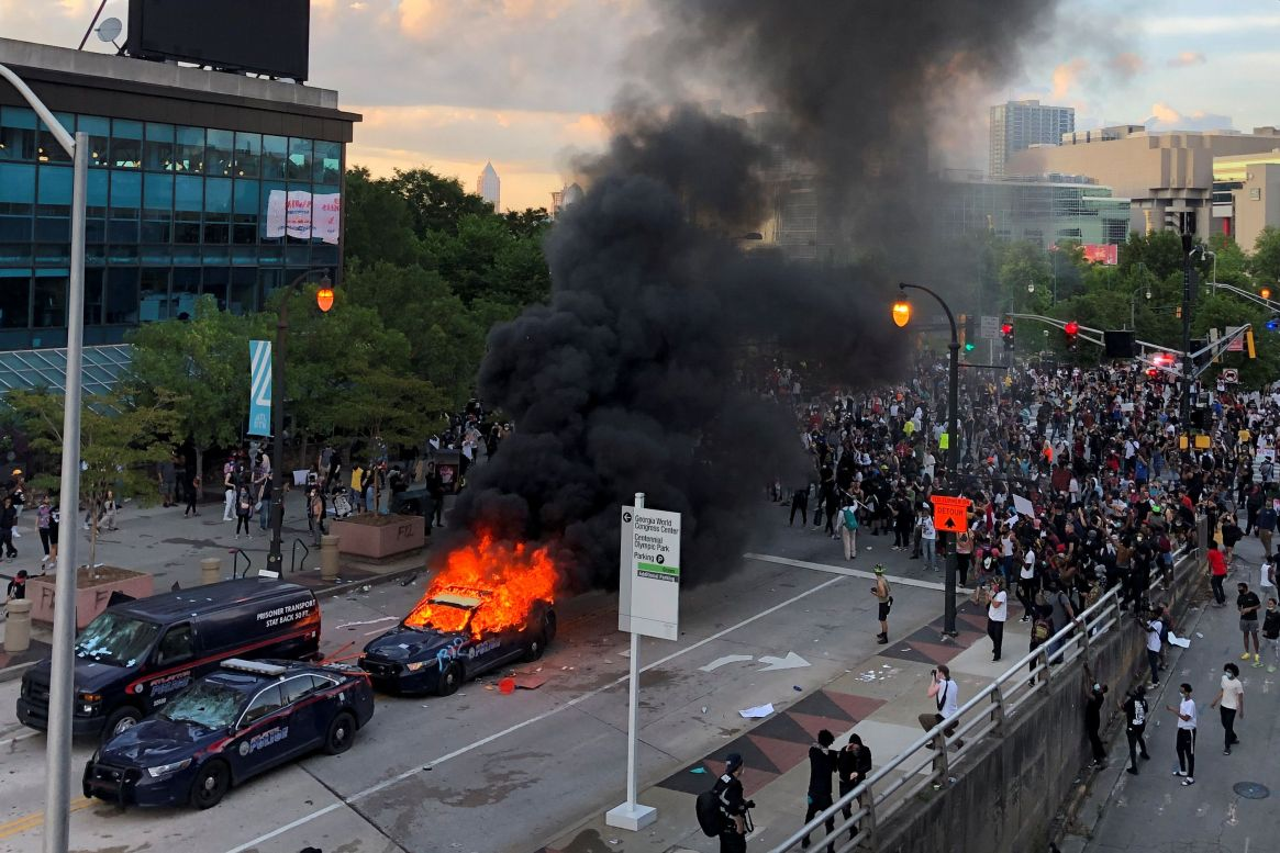 An Atlanta Police car burns as people protest against the death in Minneapolis police custody of African-American man George Floyd, near CNN Center in Atlanta, Georgia, U.S. May 29, 2020. REUTERS/Dustin Chambers