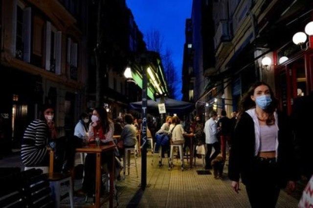 Imagen de archivo de gente con mascarillas caminando junto a clientes de un bar luego de su reapertura de en el País Vasco de España, en medio de la pandemia de COVID-19, en Bilbao, España. 19 de febrero, 2021. REUTERS/Vincent West/Archivo