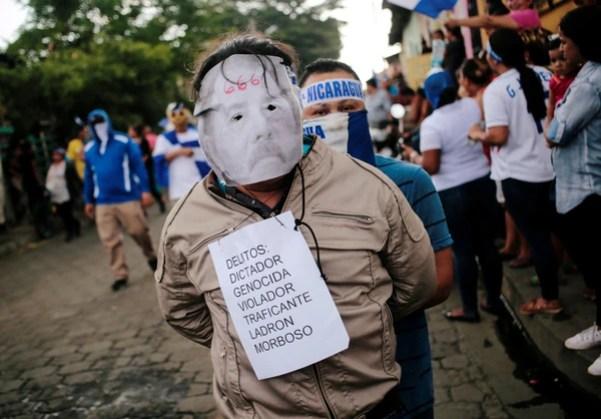 Un manifestante luce una máscara de Ortega con acusaciones de crímenes (Reuters)